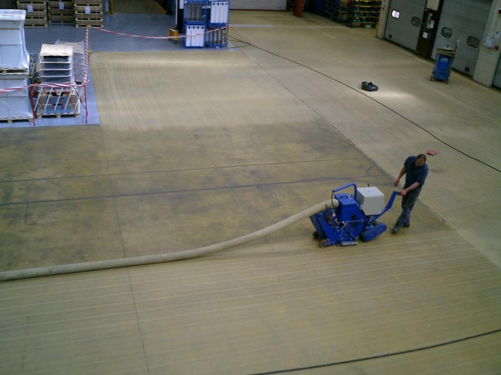 Ouvrier en train de décaper le sol avec la technique du grenaillage