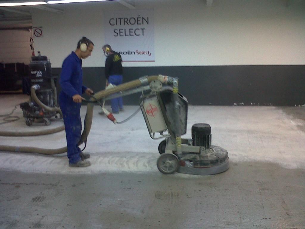 Ouvrier qui ponce une dalle de béton